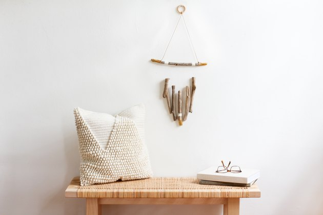 a wall hanging, made of several vertical pieces of driftwood suspended from a horizontal one, hangs above a wooden bench with a rattan top