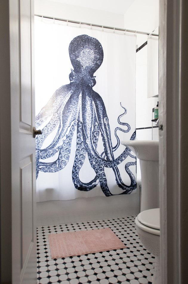 Shower curtain with a blue octopus, black-white floor tiles and a pink bathmat