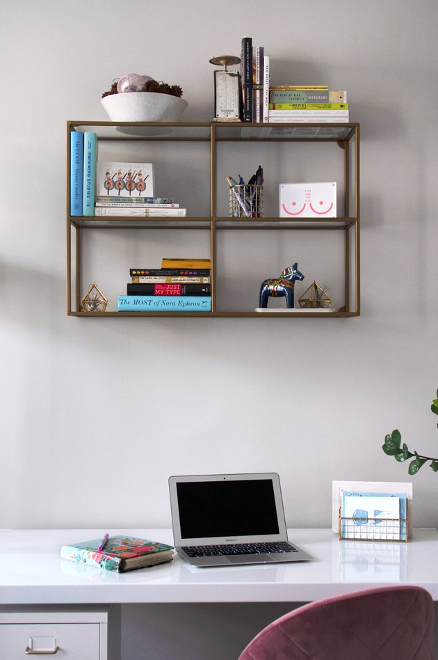 A white desk with a laptop and wall shelving with books