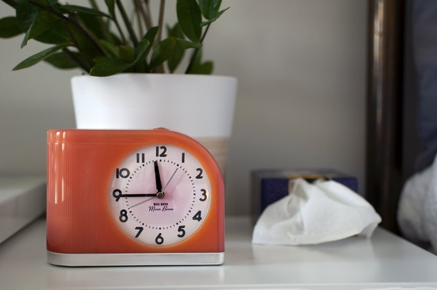 An orange retro style clock on a white desk with a plant