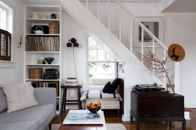 Staircase idea in living room with white walls, built in bookshelves, and dark wood farmhouse furnishings