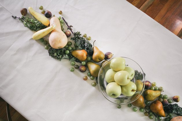 a line of produce, including grapes, pears, cherries, and squash runs down the length of a table with a white cloth