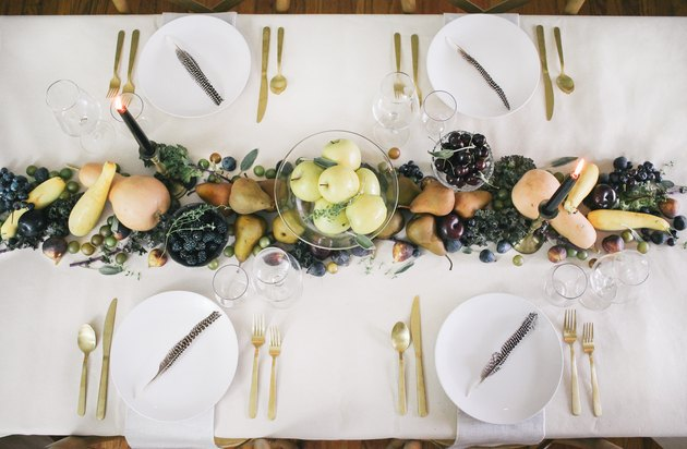 a line of produce, including grapes, pears, cherries, and squash runs down the length of a table with a white cloth and gold cutlery