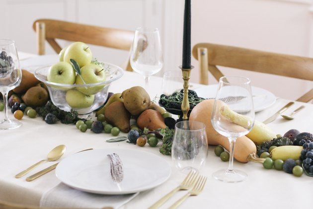 fall party idea with table runner of produce, including grapes, pears, cherries, and squash runs down the length of a table with a white cloth and gold cutlery