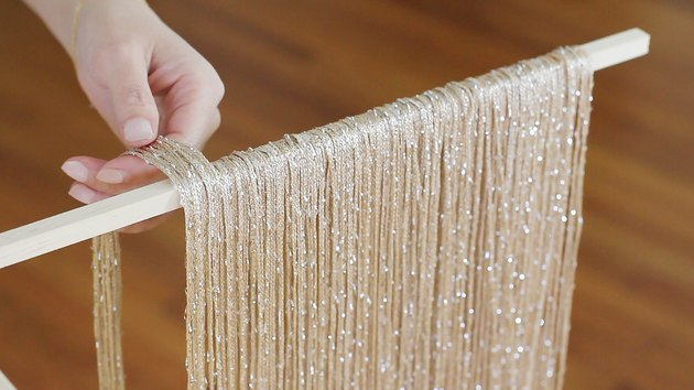 Hand placing neutral fringe curtain panels on wood dowel