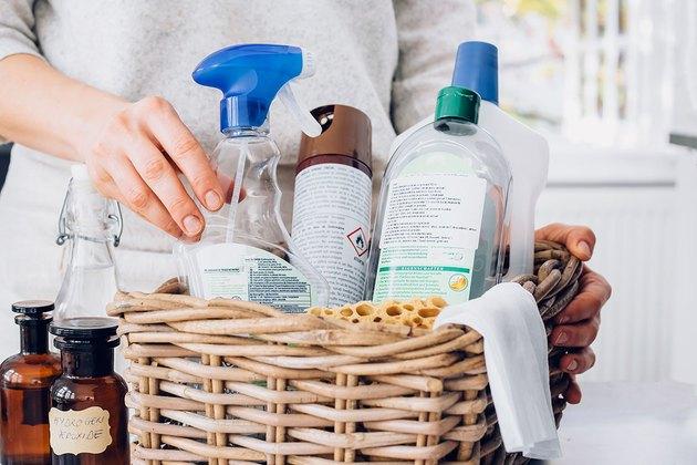 Hand adjusting basket of various cleaning liquid bottles