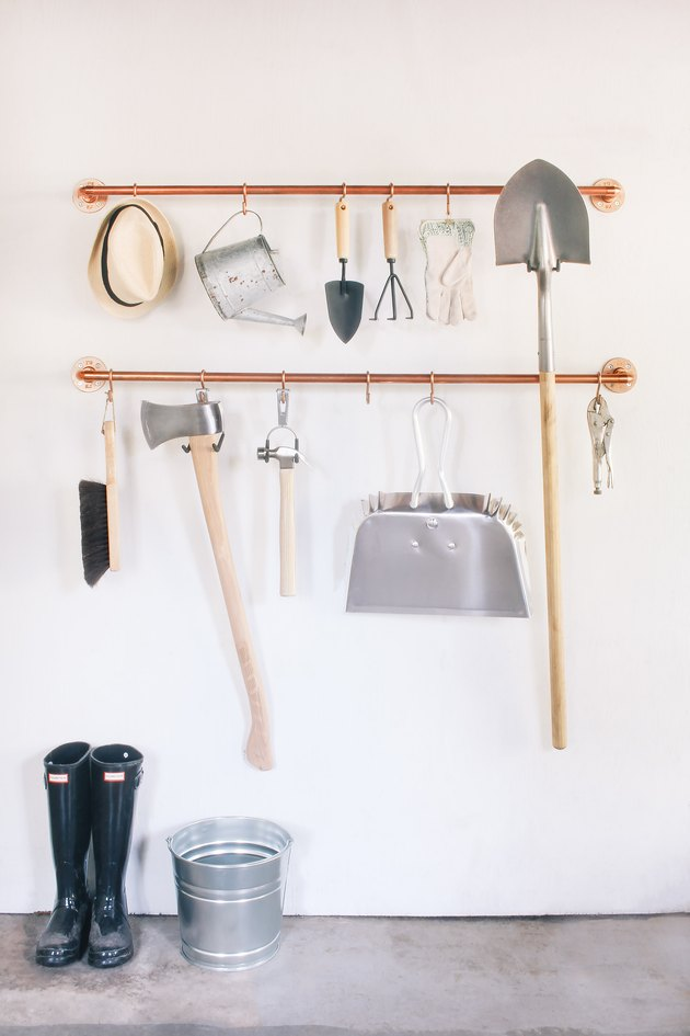 DIY garage organization idea with tools hanging on s-hooks from copper pipes mounted on a wall