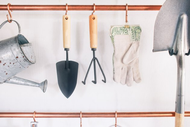 garage tools hanging on s-hooks that are suspended from copper pipes mounted on a wall