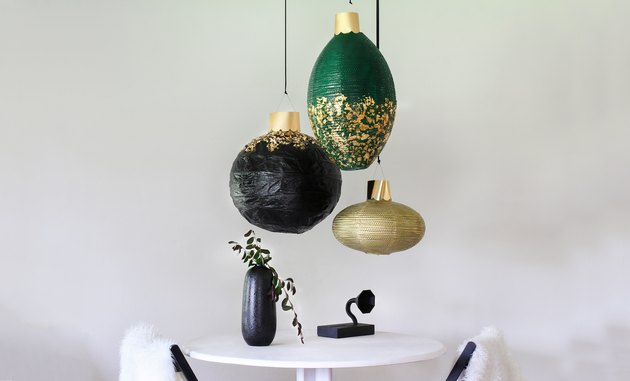 Black, green, and gold lanterns with white table and black vase