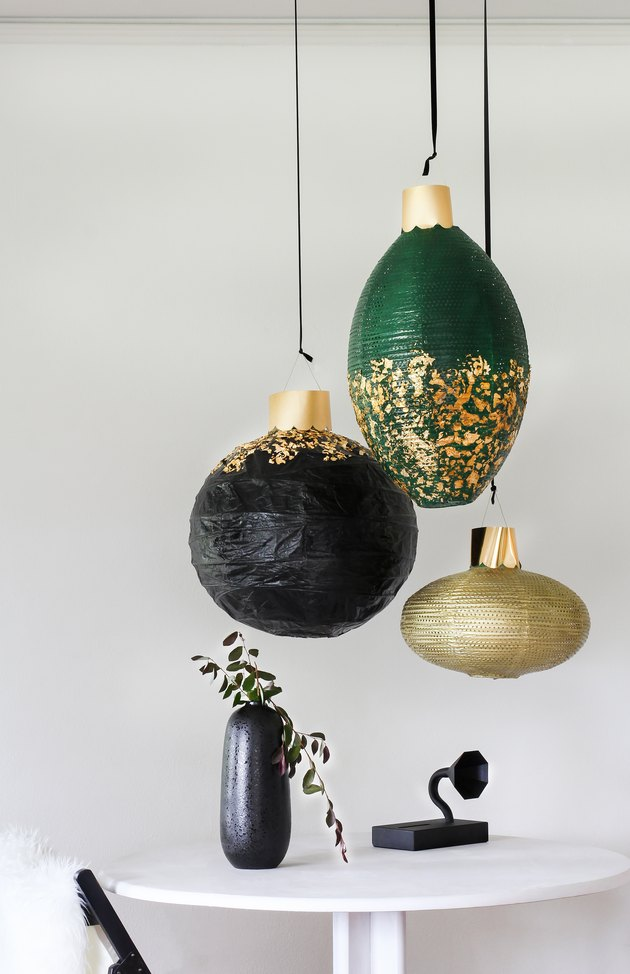 Black, green and gold lanterns above white table with black vase