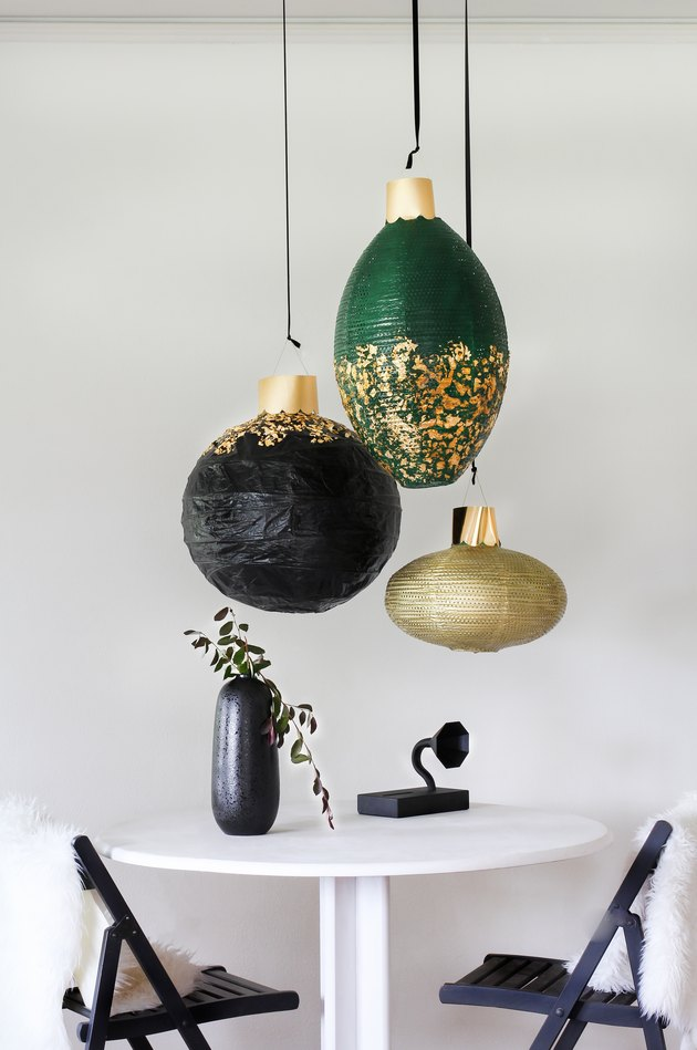 Green, gold and black lanterns with white table with black chairs and black decor
