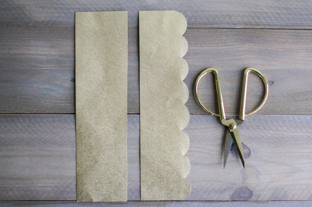 Sheets of gold paper next to gold scissors