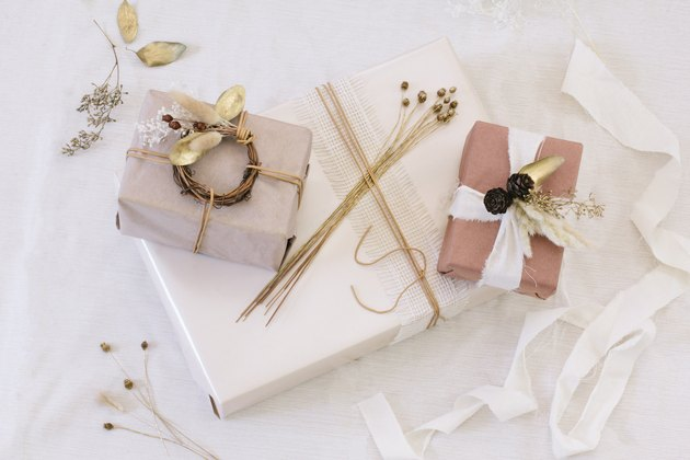 Packages with brown, white, and neutral paper with white ribbon and dried flowers