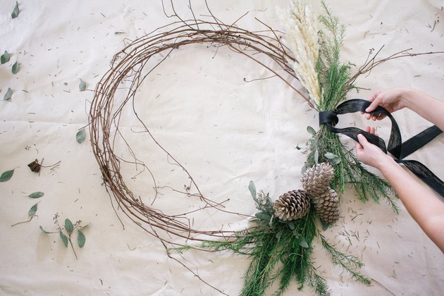 Grapevine wreath with dried plants, acorns and black ribbon