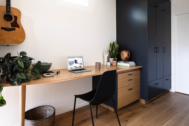 black and wood small home office idea with plants and guitar on the wall