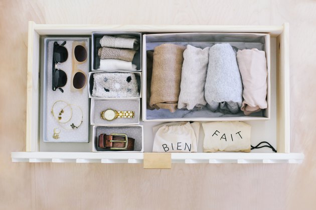 Wrapped sheets, ties, sunglasses, jewelry, and belt in variously sized hikidashi boxes in drawer against light wood background