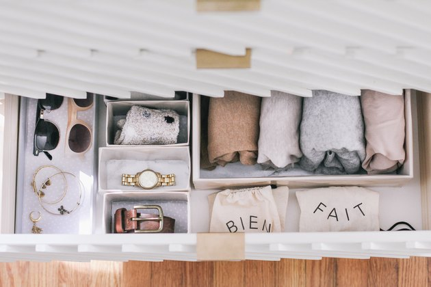 Wrapped sheets, ties, and sunglasses in DIY hikidashi boxes in open drawer of contemporary cabinet against wood flooring