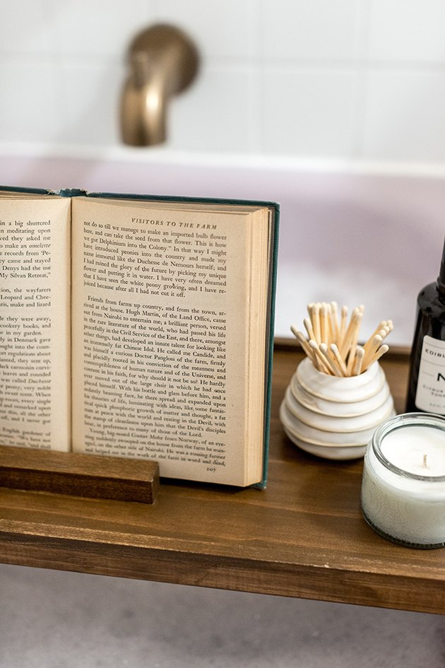 Wood bath tray with book, matches, candle over bathtub