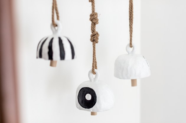 Bells made of clay, black and white paint, and rope