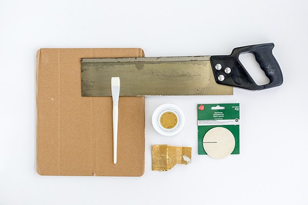 wooden disks, gold paint, a paint brush, a saw, sandpaper, and cardboard scrap