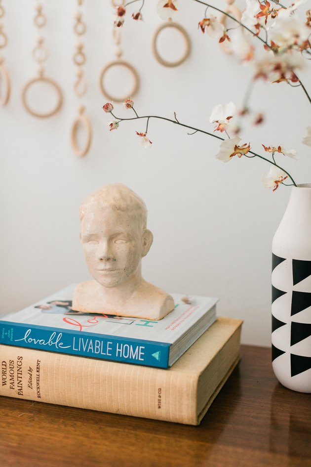 Portrait bust sculpture on books with geometric black-white vase with plant