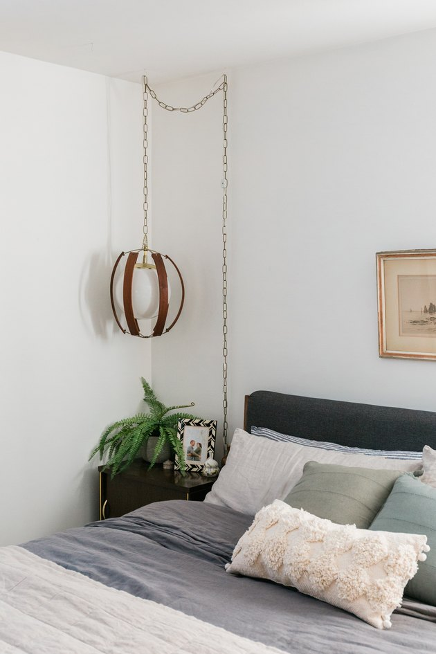 Bedroom with dark bedding, nightstand with plant, and vintage pendant lamp