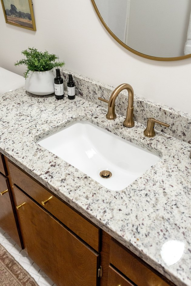 Bathroom sink with granite countertop and plant under mirror