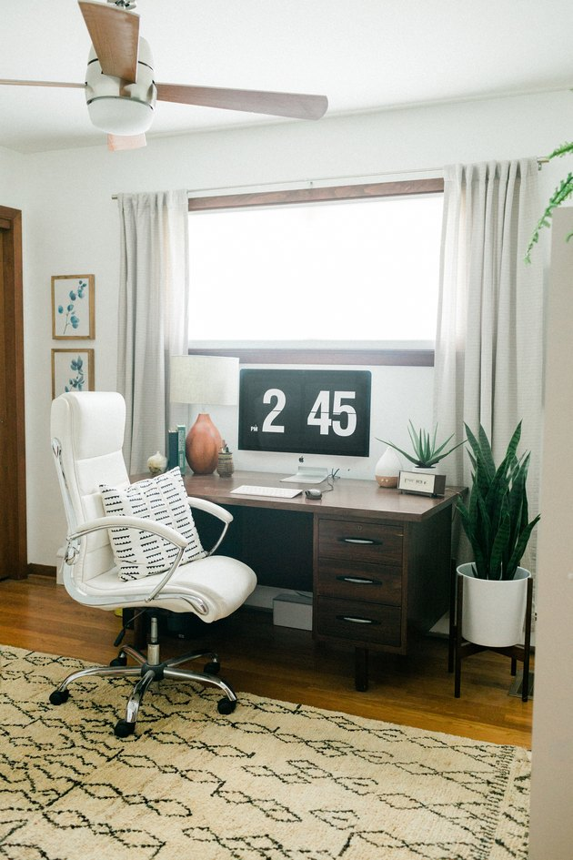 Office with tan rug, office chair, plant, and curtained window