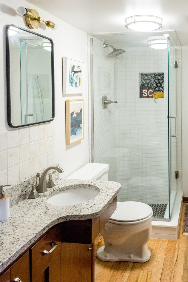 Bathroom with white wall tiles, granite vanity counter, hardwood floor, and glass door shower