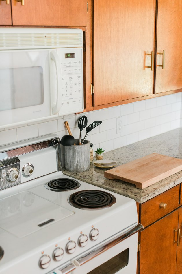 Wood kitchen cabinets, granite countertops and white tile backsplash with microwave and stovetop