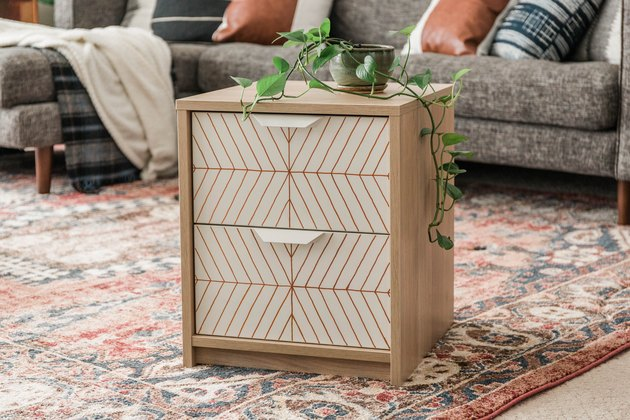Scandinavian white and neutral nightstand with striped pattern and plant on Persian rug