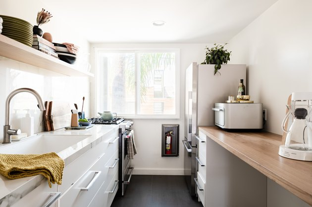a small, narrow kitchen with white drawers below and open shelving above
