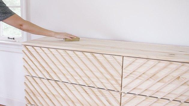Hand using sanding block on IKEA wood dresser