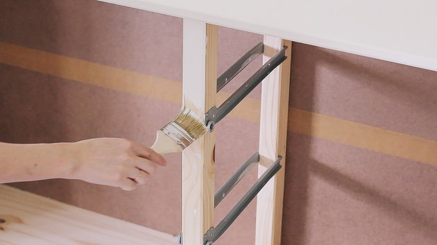 Hand with paintbrush and IKEA wood dresser