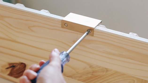 Hand using screwdriver on wood IKEA dresser