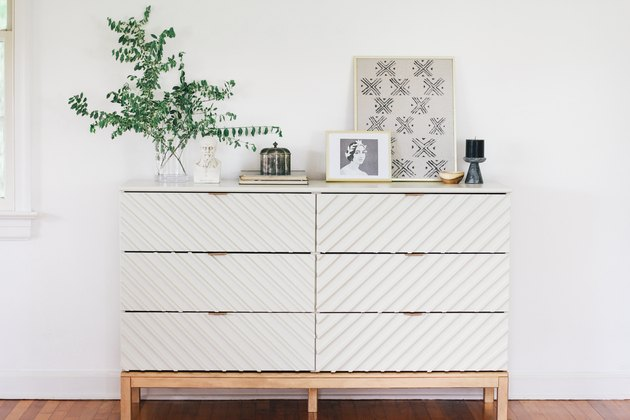 White wood IKEA dresser with plant on wood floor