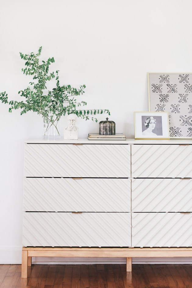 White wood dresser with plant on wood floor