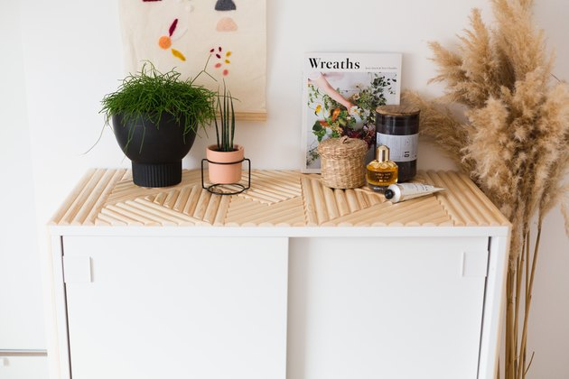 White dresser with wooden dowel pattern with plants