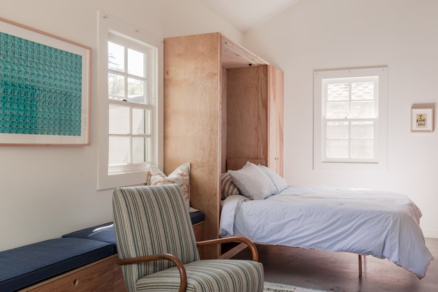 converted garage bedroom idea with murphy bed and arm chair