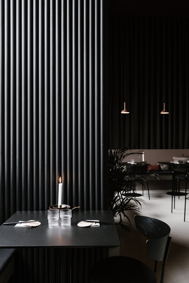 Minimalist bar with black dining furniture, pendant lights, and palm plants