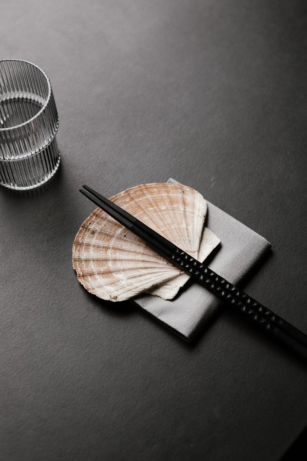 Black table with seashell supporting chopsticks next to glass