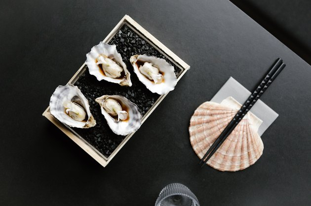 Black table with seashell supporting chopsticks with dish of oysters and a glass