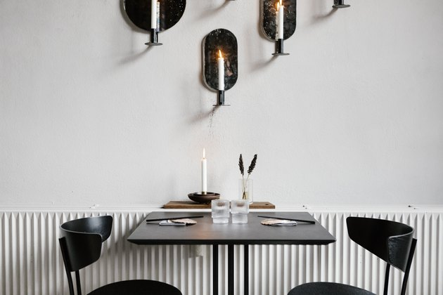 Black dining furniture next to radiator under wall with candle sconces