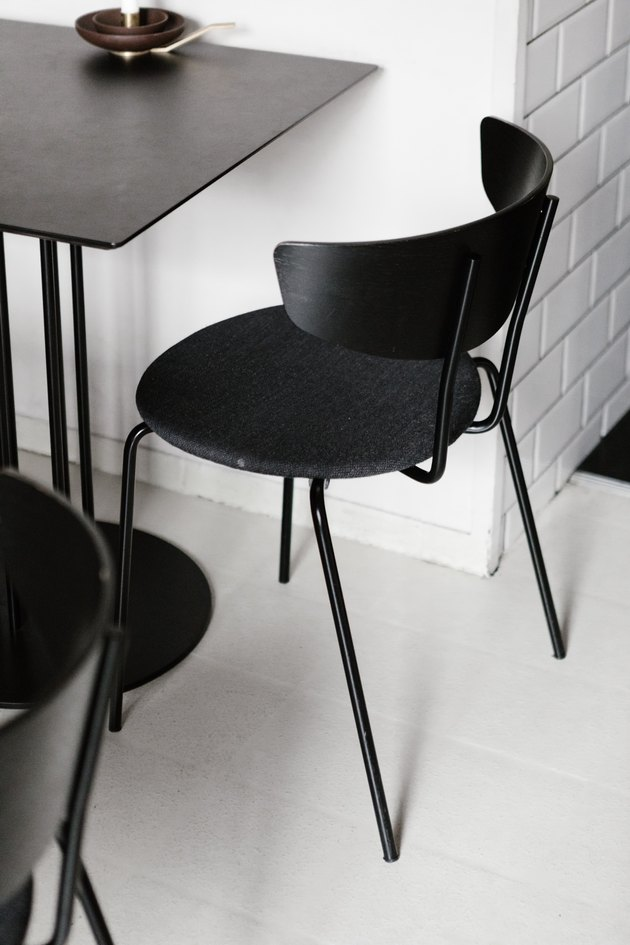 Black chair and table against white tiled wall