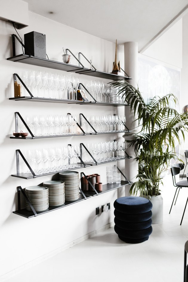 White walled Minimalist bar with shelving supporting glassware next to palm plant