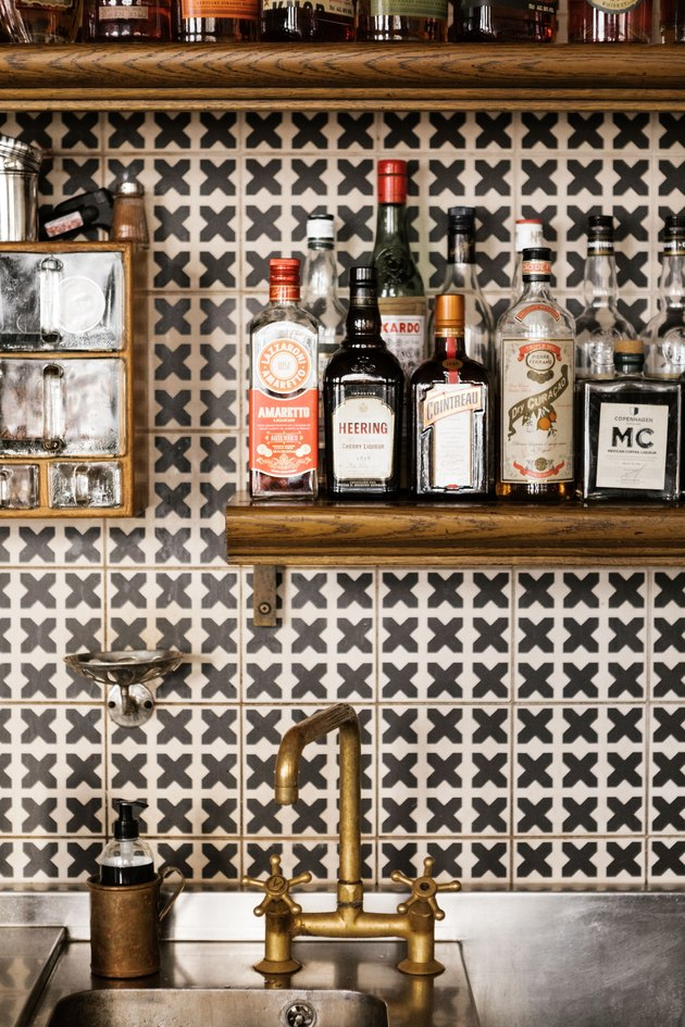 industrial bar idea with geometric backsplash, wood shelving, and industrial sink faucet
