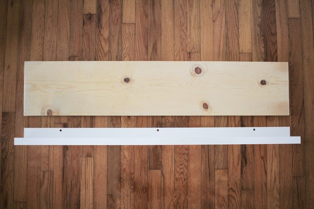 Plain plywood piece resting on wood flooring next to upright white wood piece