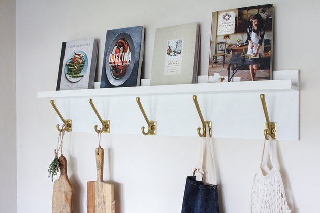 White kitchen wall hangers with gold hooks holding cutting boards, blue apron, and bag of tomatoes on white wall with books resting on top