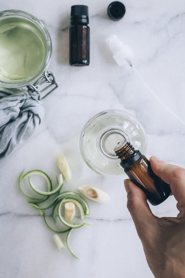 adding essential oil to a cleaning solution made of water and vinegar
