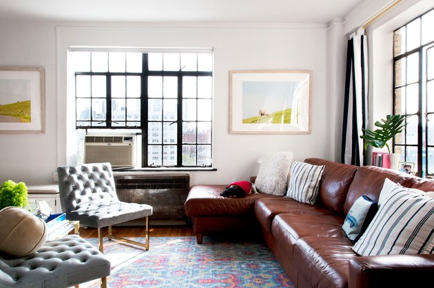 a living room is dominated by two gray upholstered chairs, a colorful pastel rug, and a leather sectional couch